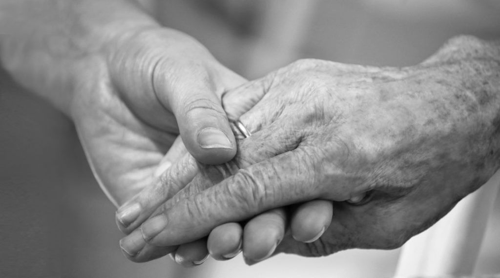 An image of a young person's hand holding an older person's hand