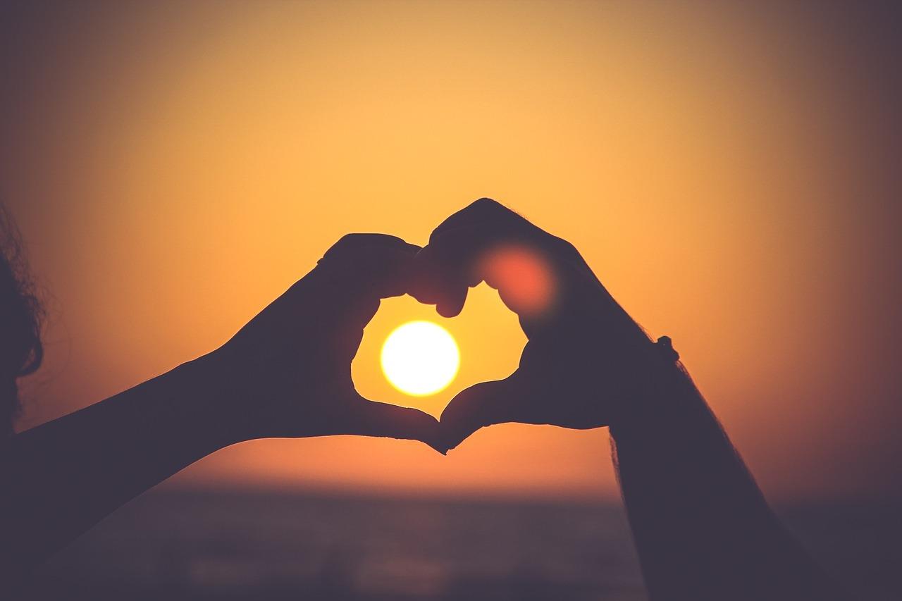 Hands making heart around sun setting